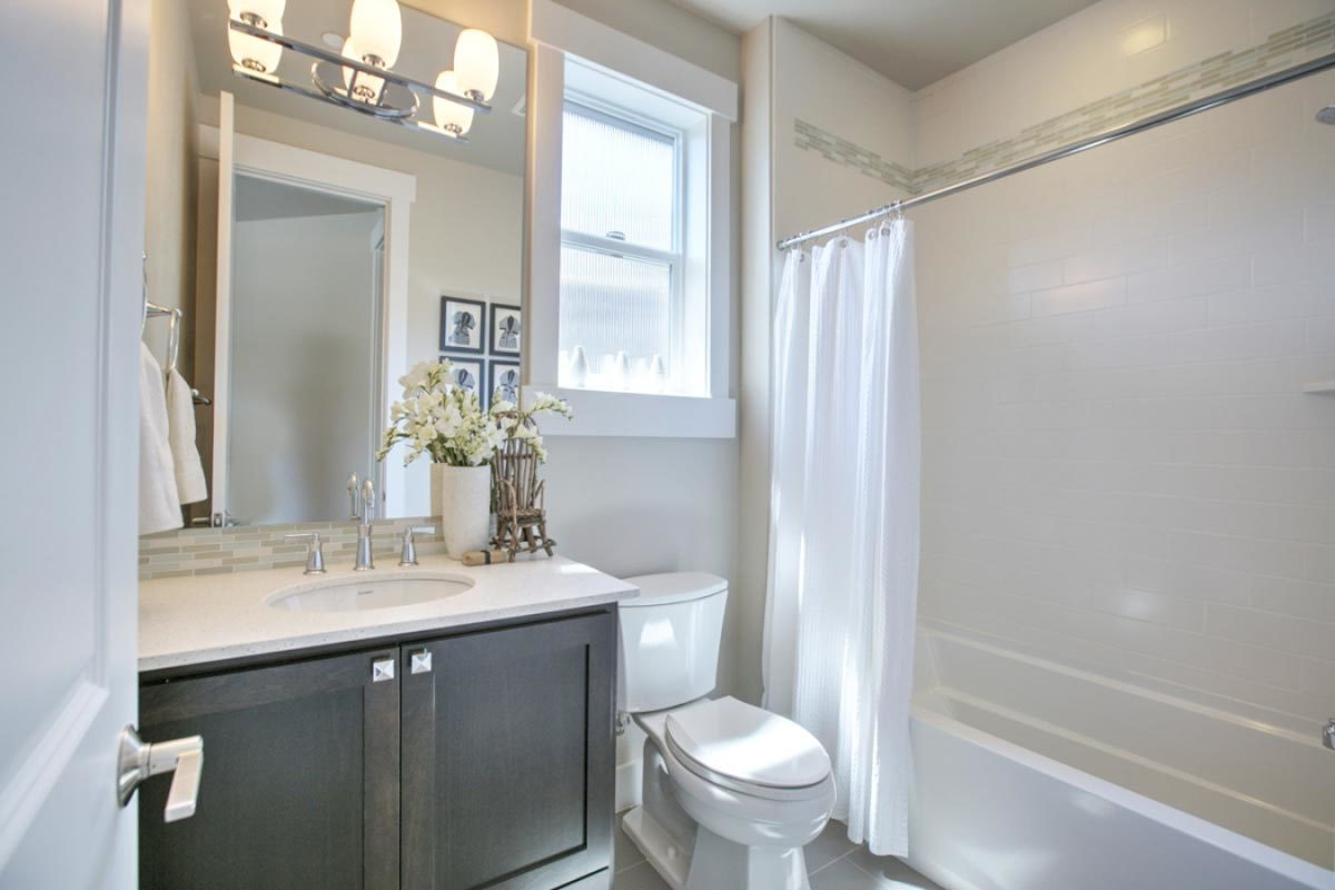 A smaller bathroom offering the same amenities. Glass sconces along with natural light from the small window illuminate the area.
