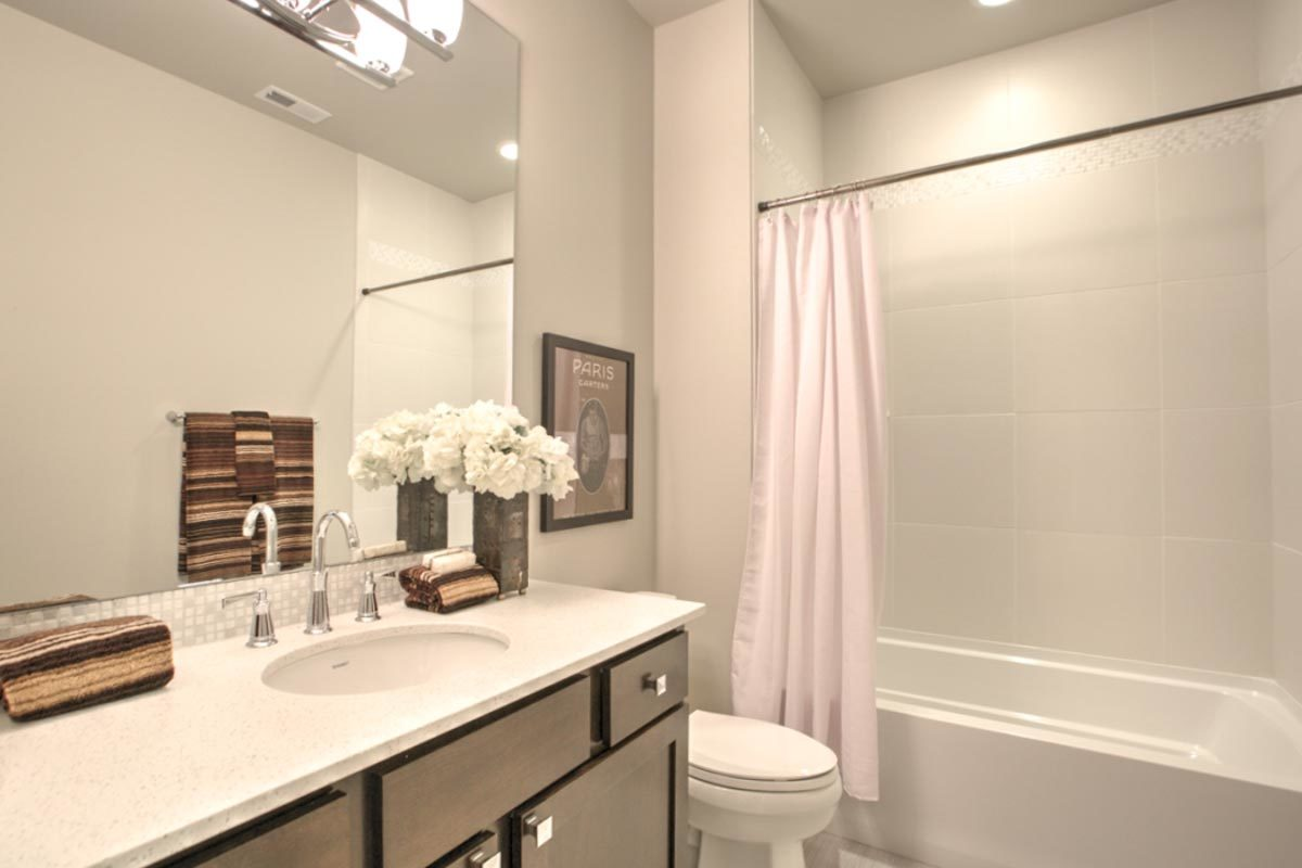 Cozy bathroom with a sink vanity, a tub and shower combo, and a toilet adorn with a black framed artwork.