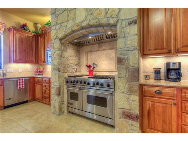 A cooking alcove adorned with gorgeous stone bricks that add texture in the kitchen.