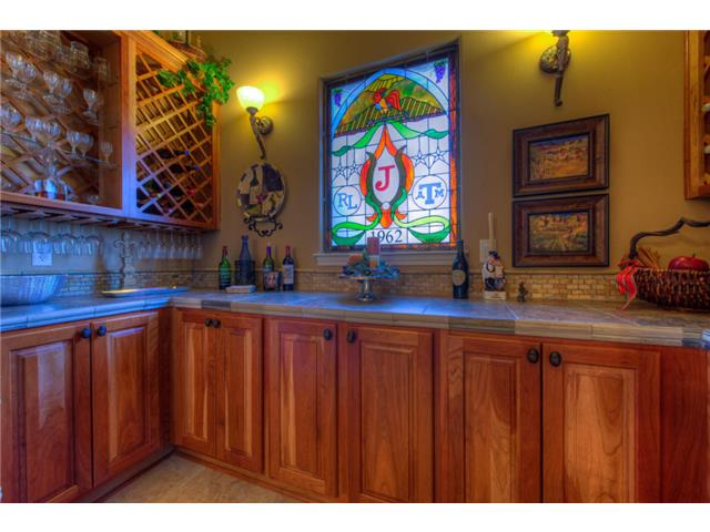 The butlery offers granite countertops, natural wood cabinets, and crisscross wine shelves fixed above the brick backsplash.
