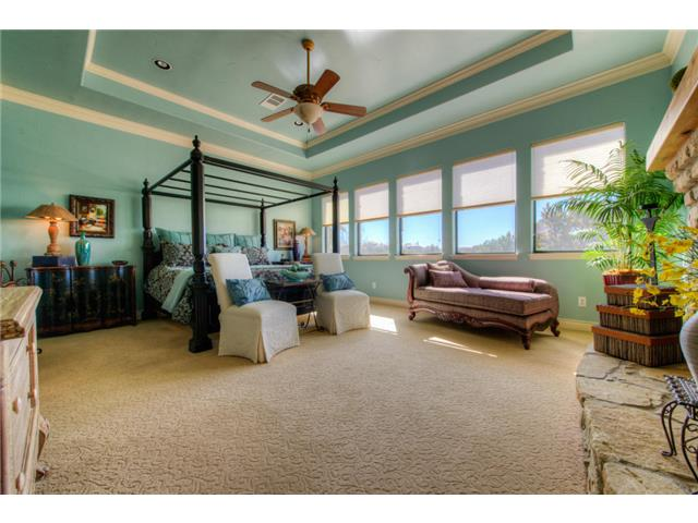 Primary bedroom with beige carpet flooring, picture windows, and a gorgeous tray ceiling mounted with a traditional fan.