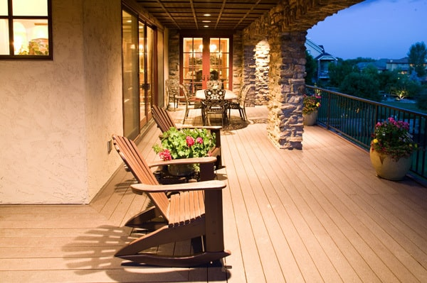 The balcony has wide plank flooring and a beamed ceiling supported by large stone pillars.