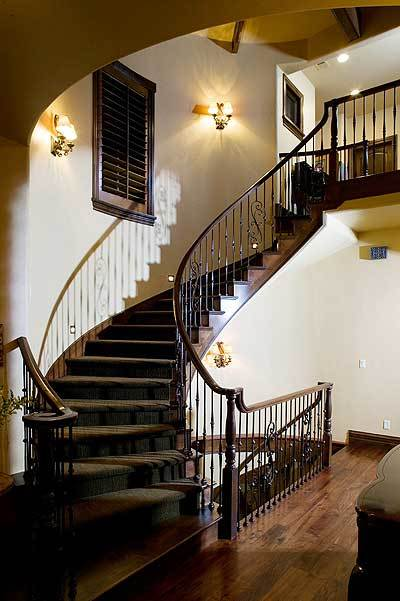 A winding staircase with ornate wrought iron railings leading to the sleeping areas.