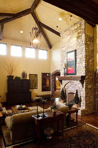 The living room offers a comfy sofa and chair, wooden tables, a stone fireplace, and a warm glass chandelier hanging from the beamed ceiling.