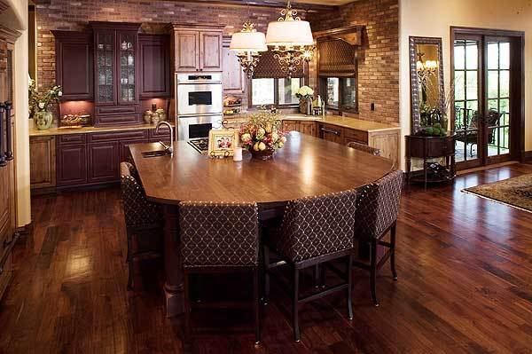 Kitchen with wooden cabinetry, intricate drum pendants, and a large center island surrounded by patterned counter chairs.