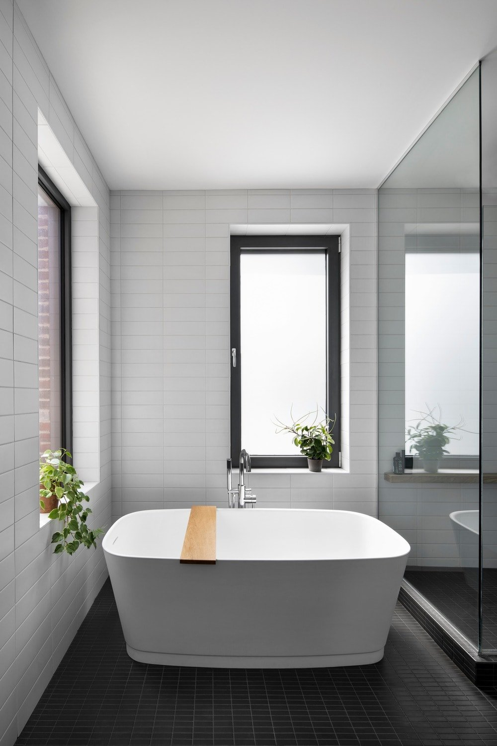 This is the bathroom that has a white freestanding bathtub to contrast the black flooring tiles and the glass wall of the shower area beside it.