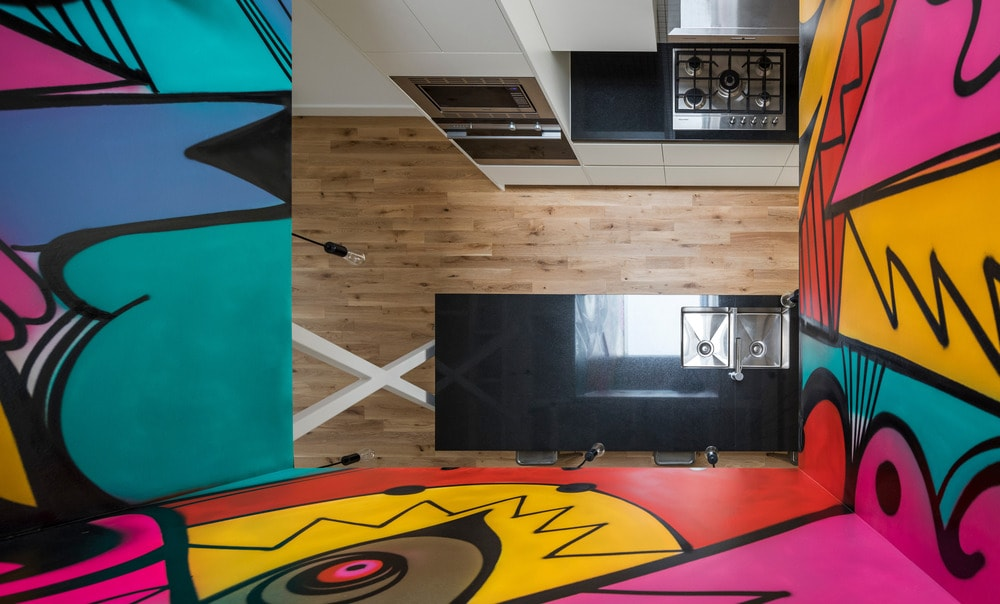 This is a look at the kitchen from the vantage of the indoor balcony of the upper level adorned with colorful murals.