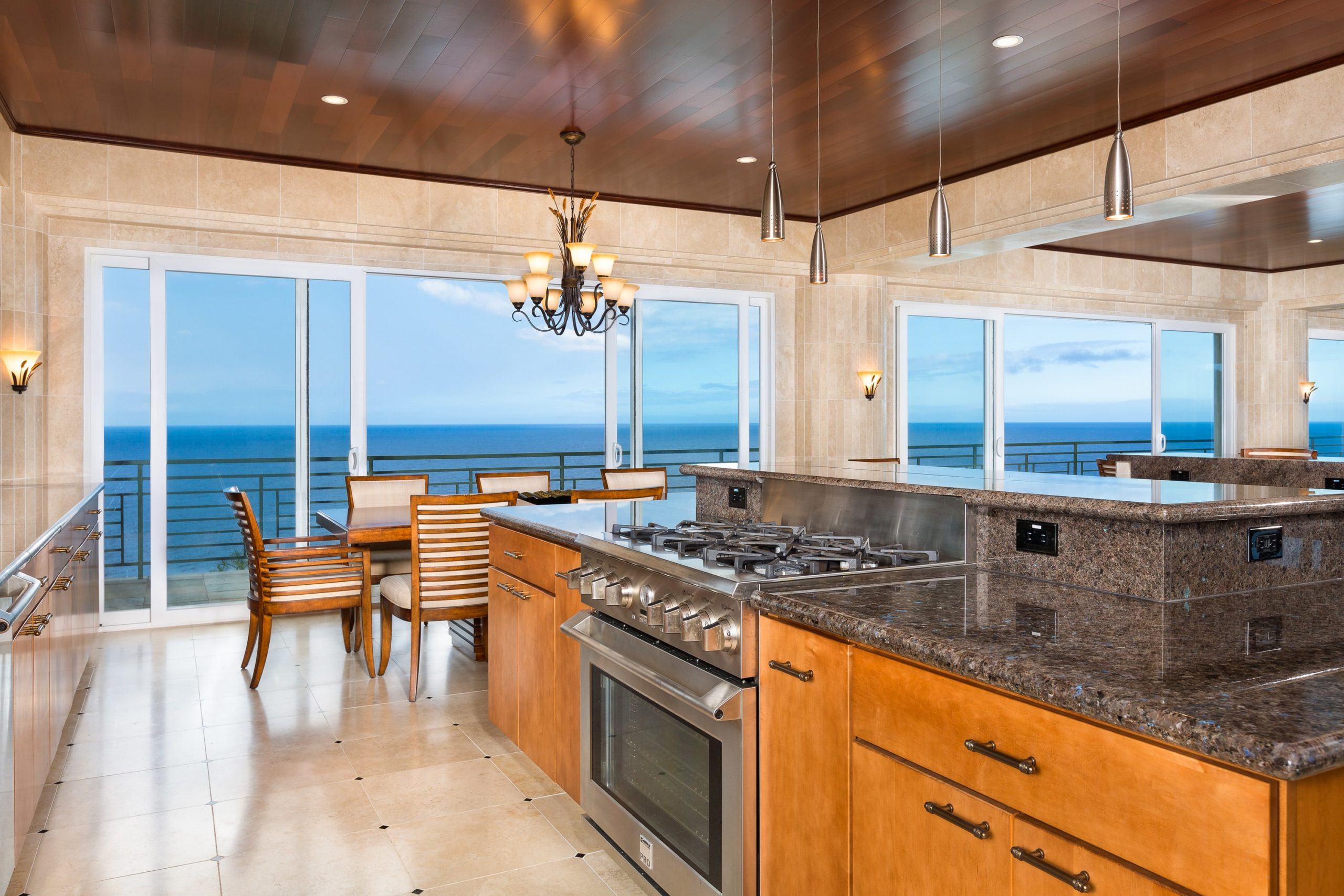 The kitchen has granite countertops, a breakfast bar, stainless steel appliances, and a view to the ocean. Image courtesy of Toptenrealestatedeals.com.