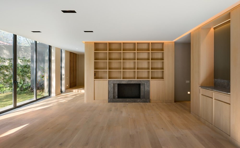 This is the living room area with a hardwood flooring that extends to the built-in wooden structure surrounding the fireplace at the far end.