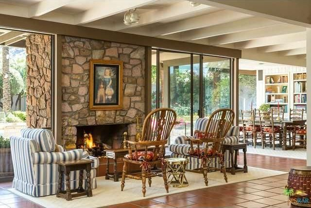 A stone fireplace has a painting at the center and faces a wooden small table and armchairs. Image courtesy of Toptenrealestatedeals.com.