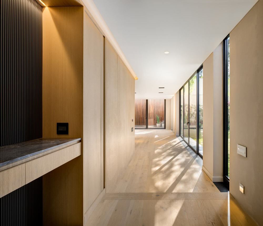 This is the halllway leading from the living room area. You can see here the wooden tone of the walls match with the hardwood flooring that is illuminated by the white ceiling and glass walls.