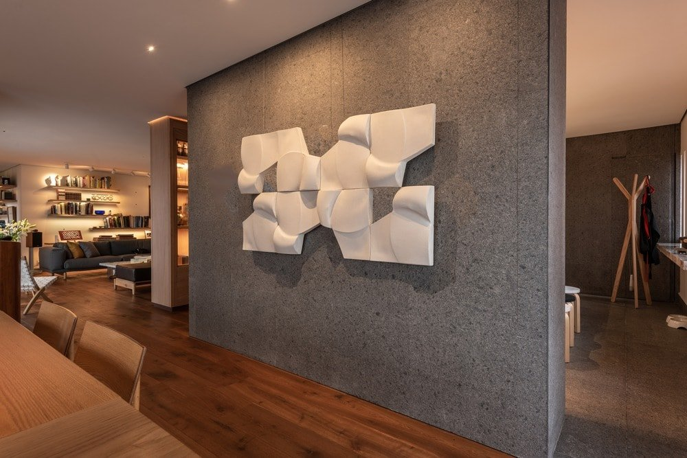 On the side of the dining area is this large concrete wall adorned with a decorative wall-mounted art piece.