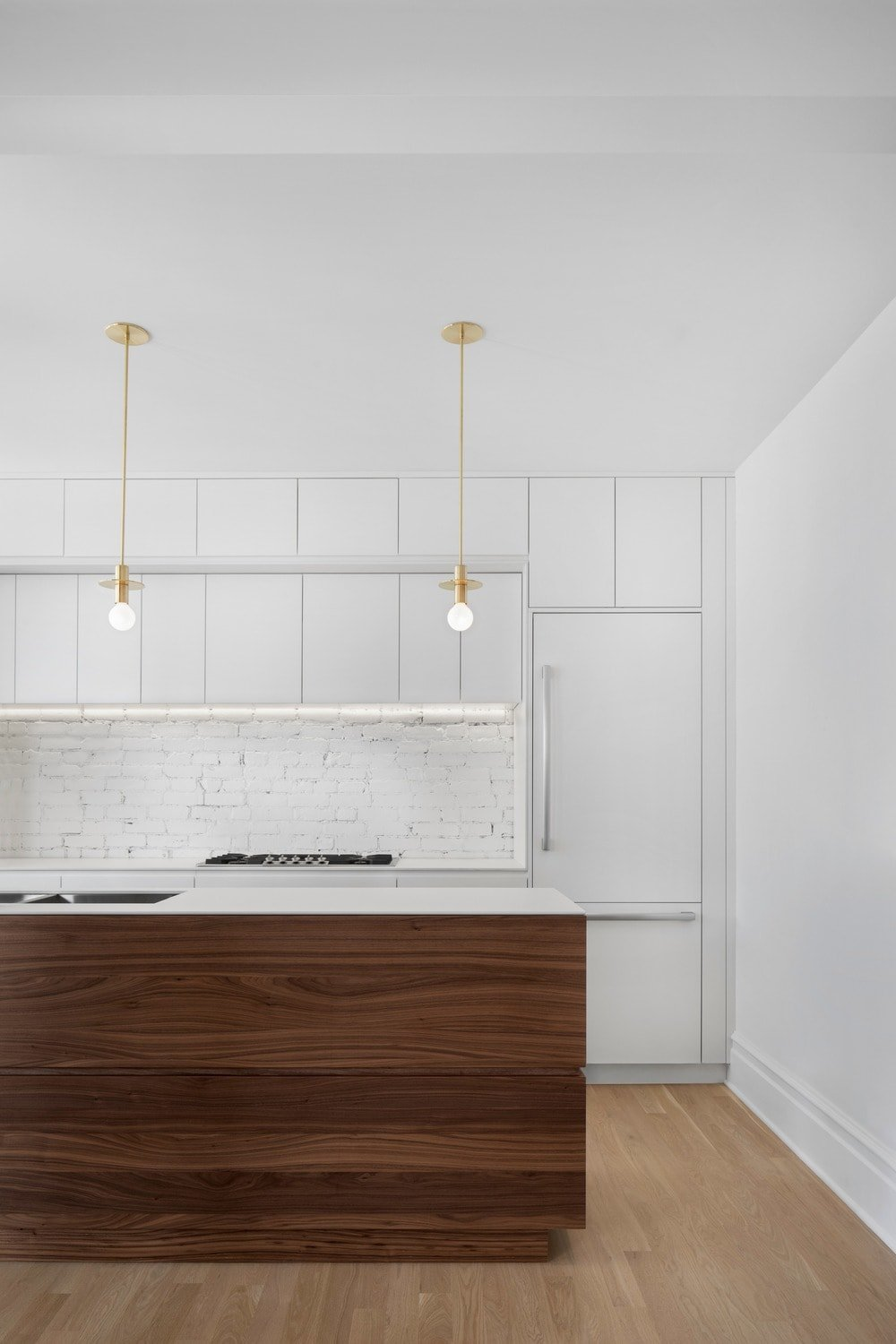 This other look at the kitchen shows the modern cabinetry lining the wall across from the kitchen island, This is paired with a white brick backsplash.