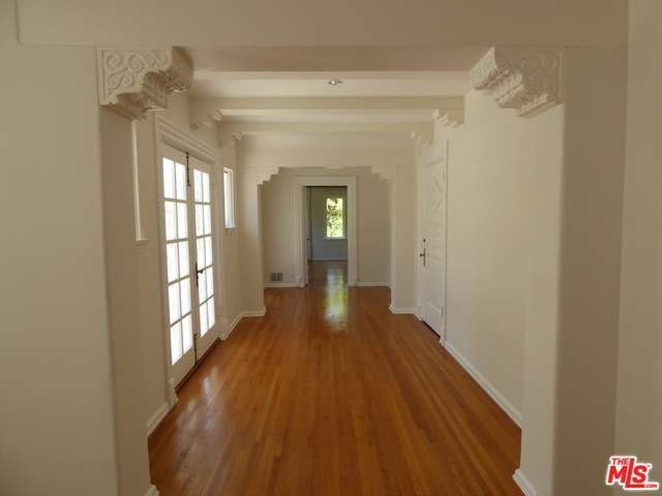 Hallway with crown molding, wood flooring, and French doors. Image courtesy of Toptenrealestatedeals.com.
