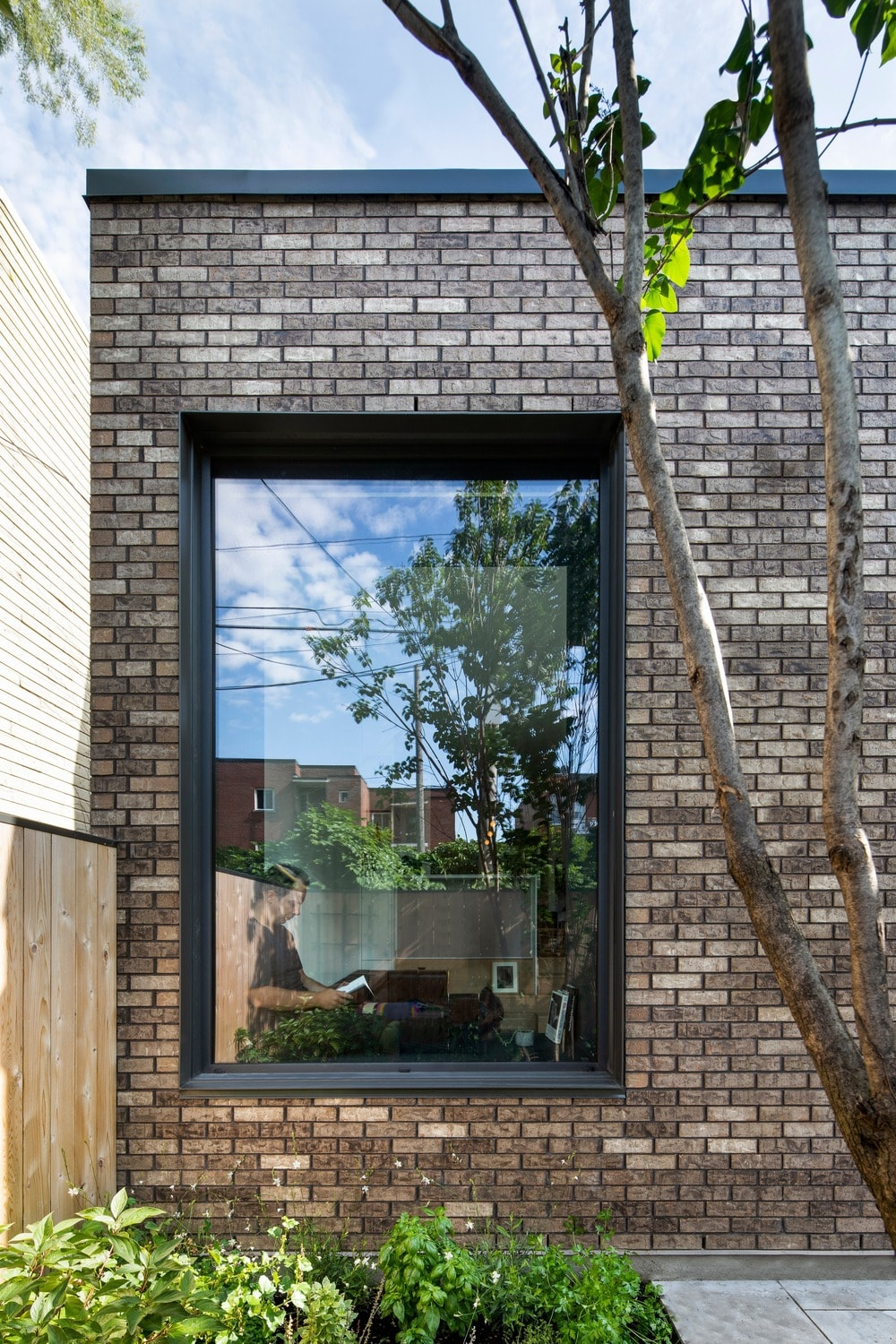 This is an external look at the large glass window that stands out against the brick exterior wall adorned with shrubs and a tree on the side.