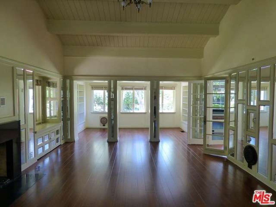 An empty white room with beam ceiling, glass doors, and wood flooring. Image courtesy of Toptenrealestatedeals.com.