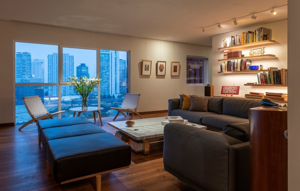 This is the living room that has a dark gray sofa set paired with a low marble-top coffee table and floating bookshelves on the wall.