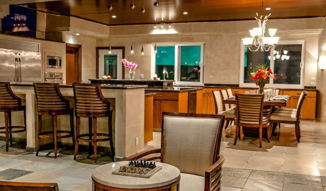 The game room also has a card table and a view to the kitchen and dining area. Image courtesy of Toptenrealestatedeals.com.