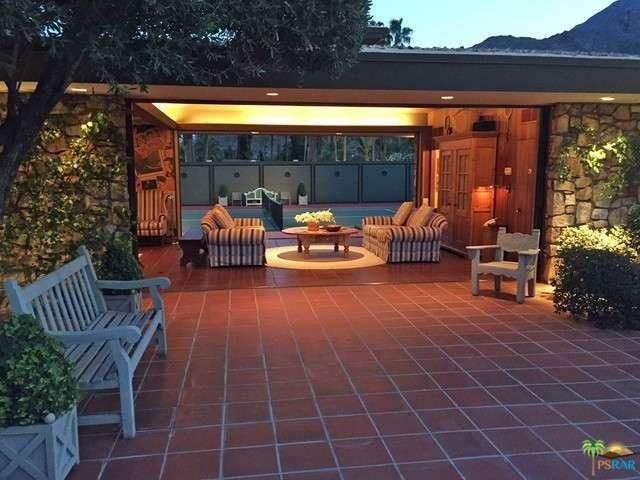 A covered patio with sofas and a round table on red brick flooring and a view to the tennis court. Image courtesy of Toptenrealestatedeals.com.