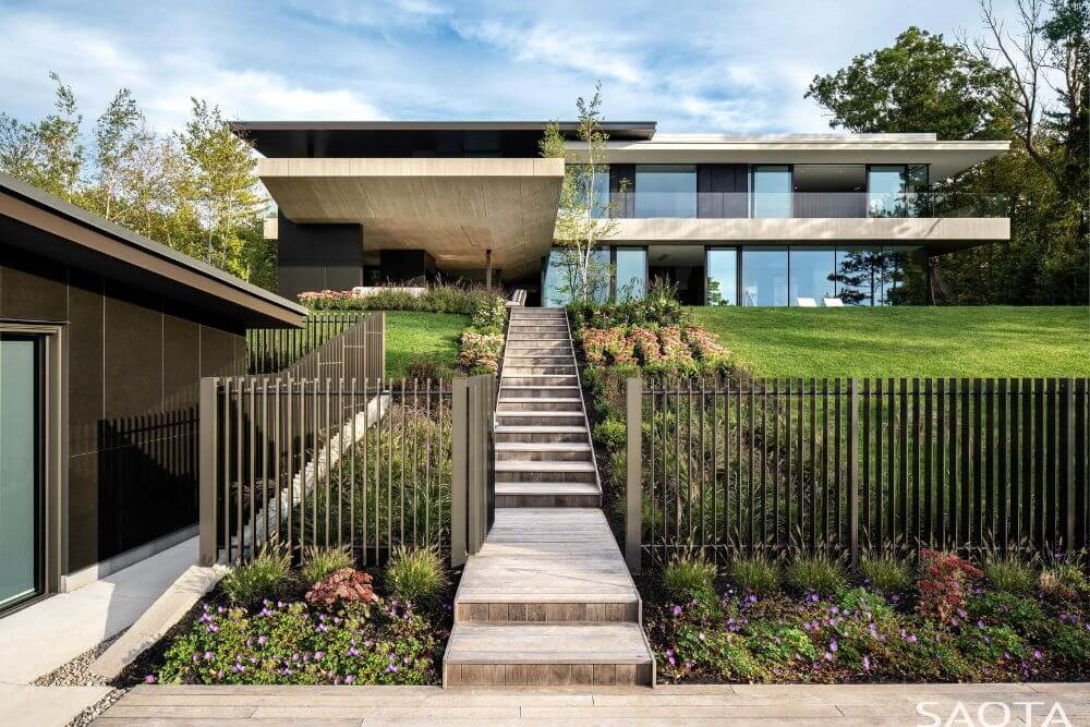 This is a look at the front of the house with a set of concrete steps flanked by flowering shrubs and grass lawns leading to the main entrance.