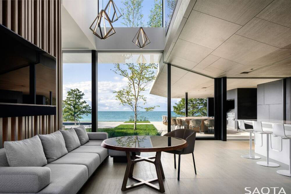 This is the living room that has a tall ceiling and a view of the landscape outside the glass doors to the poolside area.