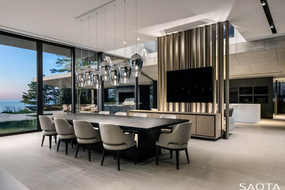 The dining area has a large dark wooden dining table surrounded by light gray cushioned chairs and topped with a set of modern decorative lighting.