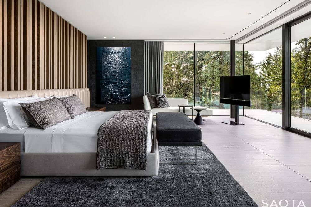 The bedroom has a cushioned headboard that extends to the bedside drawers. These are complemented by the surrounding glass walls that offer views of the landscape outside.