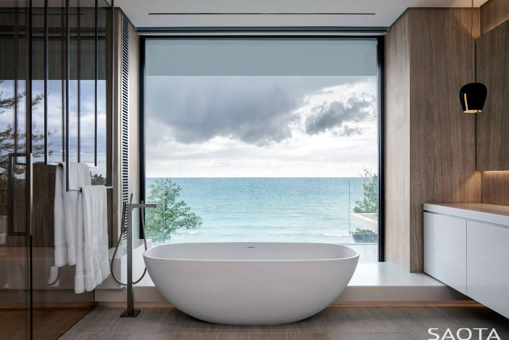 This is the bathroom with a freestanding bathtub at the far end by the large glass wall that offers a view of the lake.
