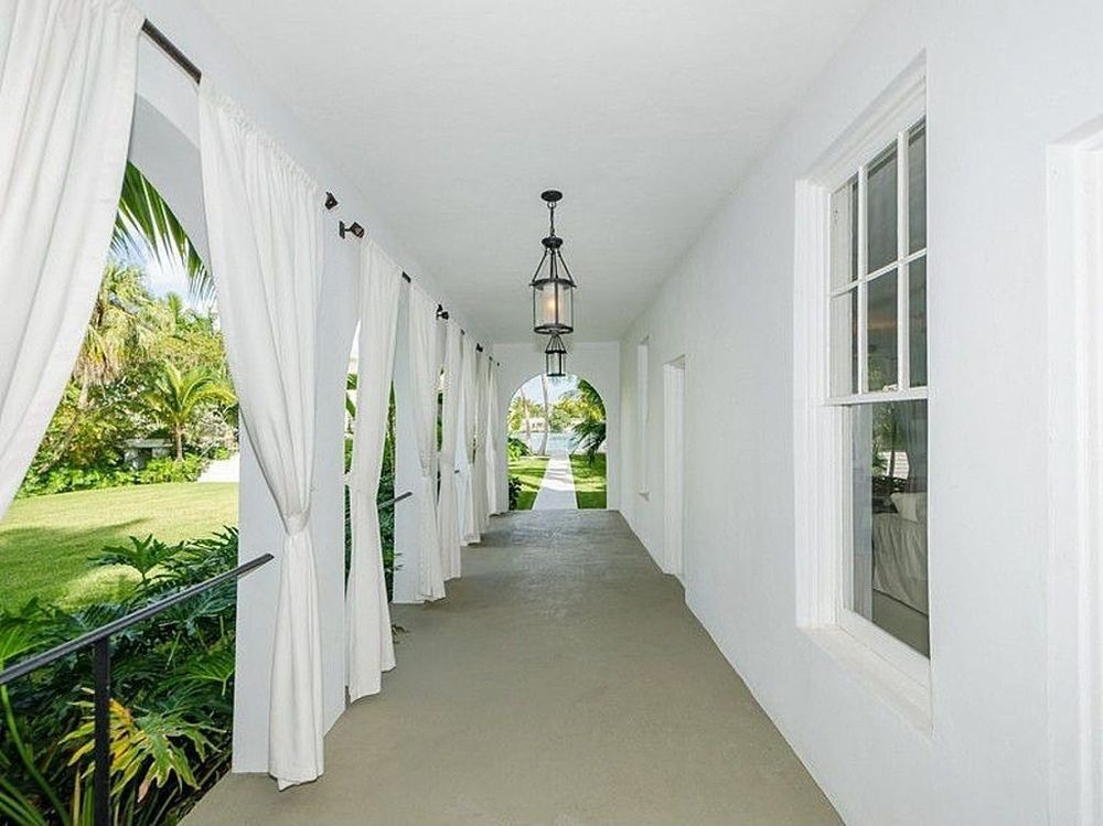 Hallway of the house with white curtains and pendant lights. Images courtesy of Toptenrealestatedeals.com.