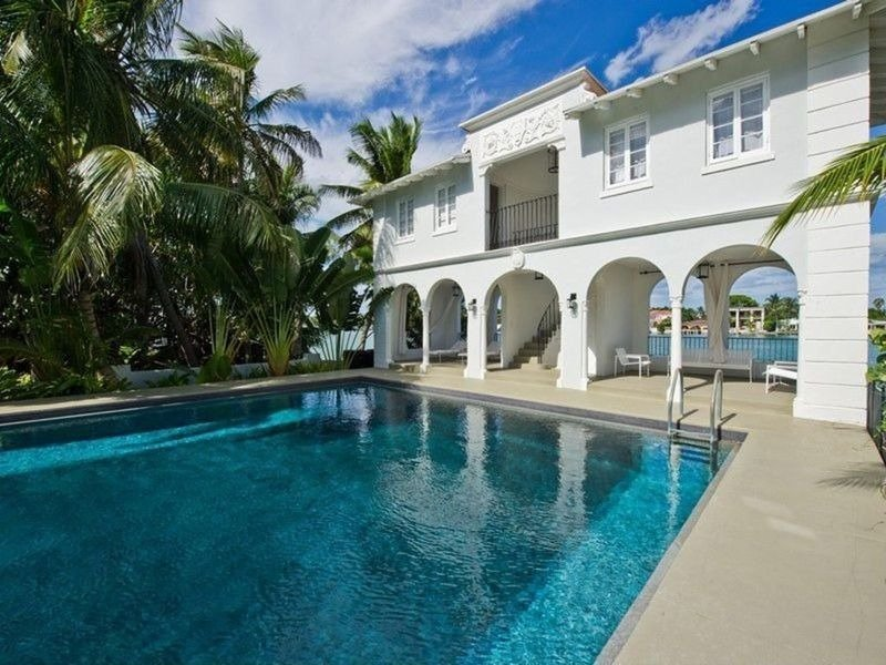 A swimming pool with a pool house and tropical trees on the side. Images courtesy of Toptenrealestatedeals.com.
