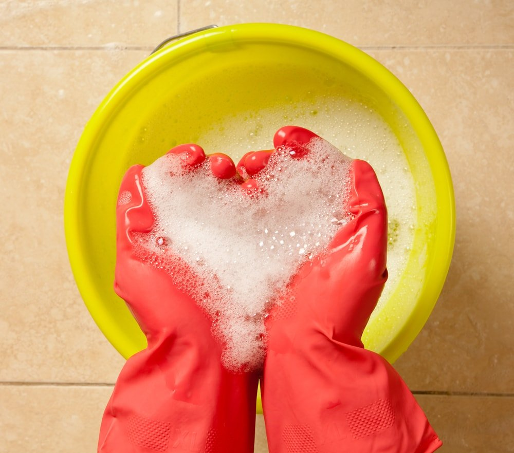A pair of gloved hands with soapy water and a bucket.