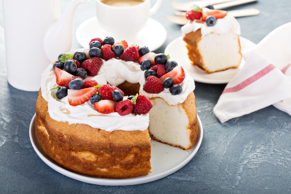 A freshly-made Angel Food Cake with berries for toppings.