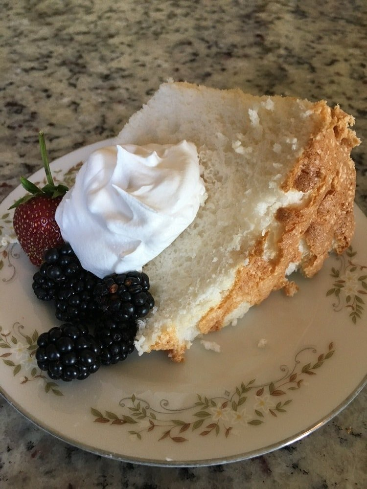 A slice of Angel Food Cake with berries and frosting on the side.