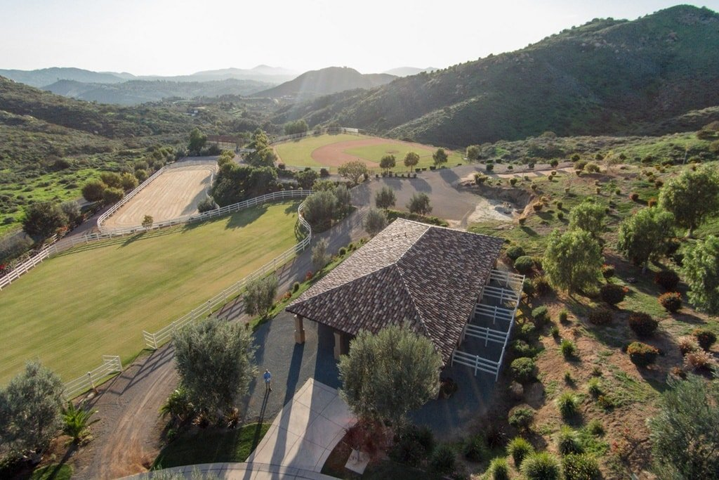 This is an aerial view of the property showing the mediterranean-style main home along with the pro-style baseball field on the far side surrounded by tall trees and hills. Image courtesy of Toptenrealestatedeals.com.