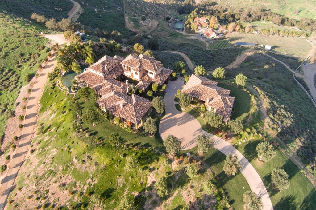 This aerial view of the house shows its wide driveway surrounded by landscaping filled with tall trees and grass. Image courtesy of Toptenrealestatedeals.com.