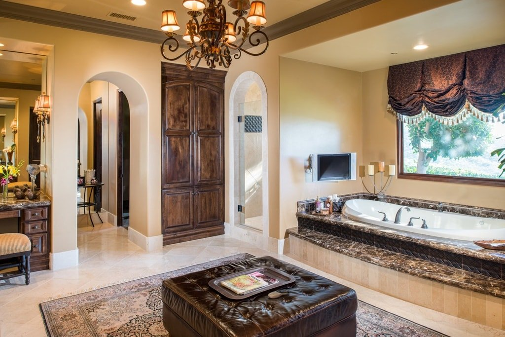 This is the primary bathroom with beige walls, ceiling and floor. These make the dark brown door, ottoman and chandelier stand out. On the far side is the bathtub under the window. Image courtesy of Toptenrealestatedeals.com.