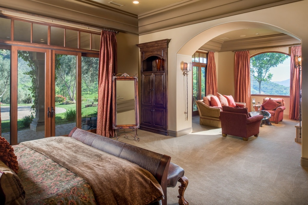 The primary bedroom has a sitting area across from the bed through an arched entryway. This has cushioned armchairs that pair well with the surrounding window curtains. Image courtesy of Toptenrealestatedeals.com.