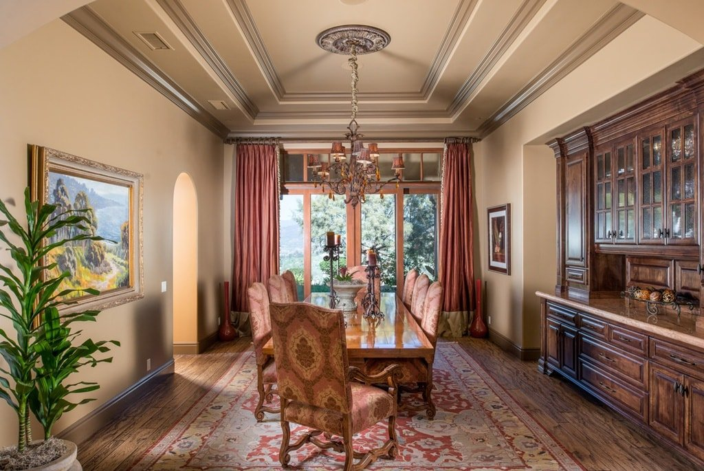 The formal dining room has a cove ceiling that hangs a chandelier over the large rectangular dining table surrounded by cushioned chairs that match the area rug. Image courtesy of Toptenrealestatedeals.com.
