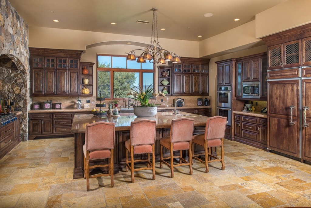 This is the kitchen with a large kitchen island in the middle of its beige-tiled floor that matches the ceiling. These make the dark brown wooden cabinetry stand out. Image courtesy of Toptenrealestatedeals.com.