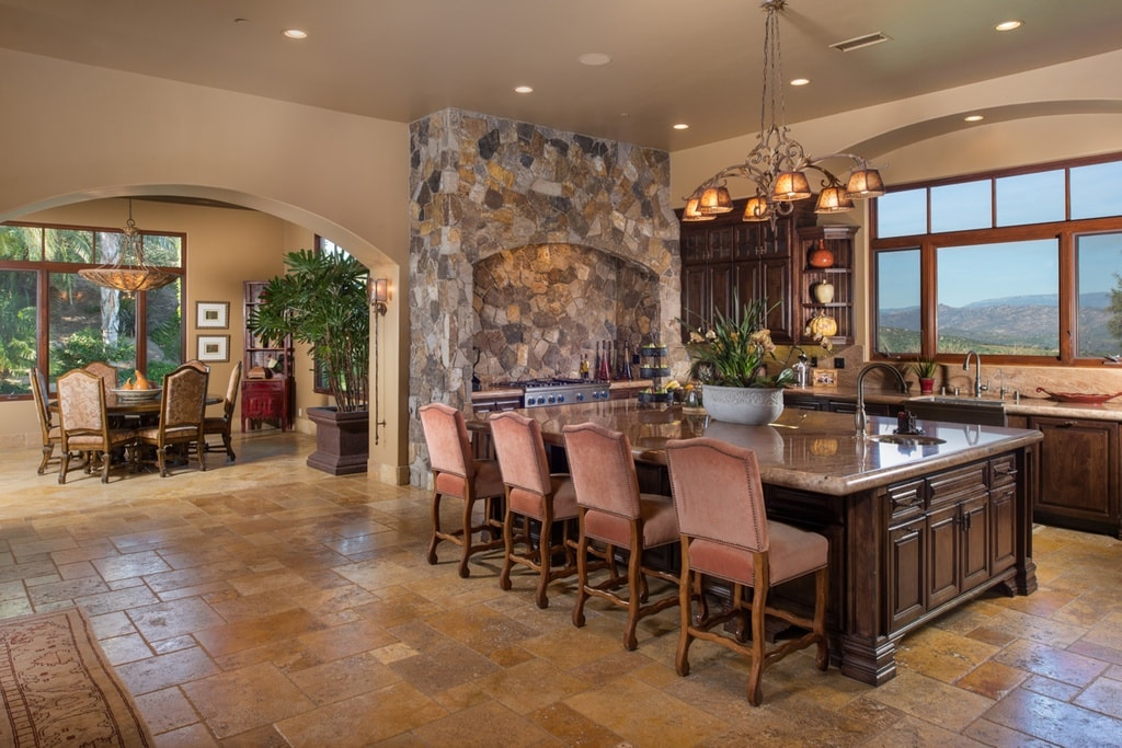 This view of the kitchen shows the mosaic stone alcove of the cooking area. On the side of this is the wide arched entryway to the informal dining area. Image courtesy of Toptenrealestatedeals.com.
