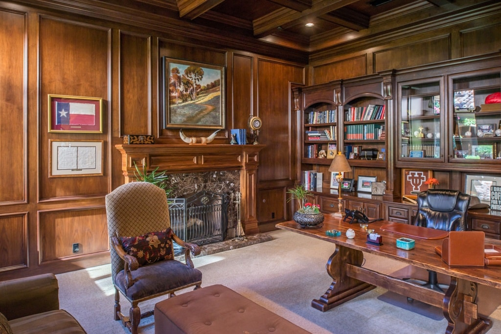 The library has a consistent dark wooden tone to its walls, coffered ceiling, fireplace mantle that built-in bookshelves lining the wall on one side. Image courtesy of Toptenrealestatedeals.com.