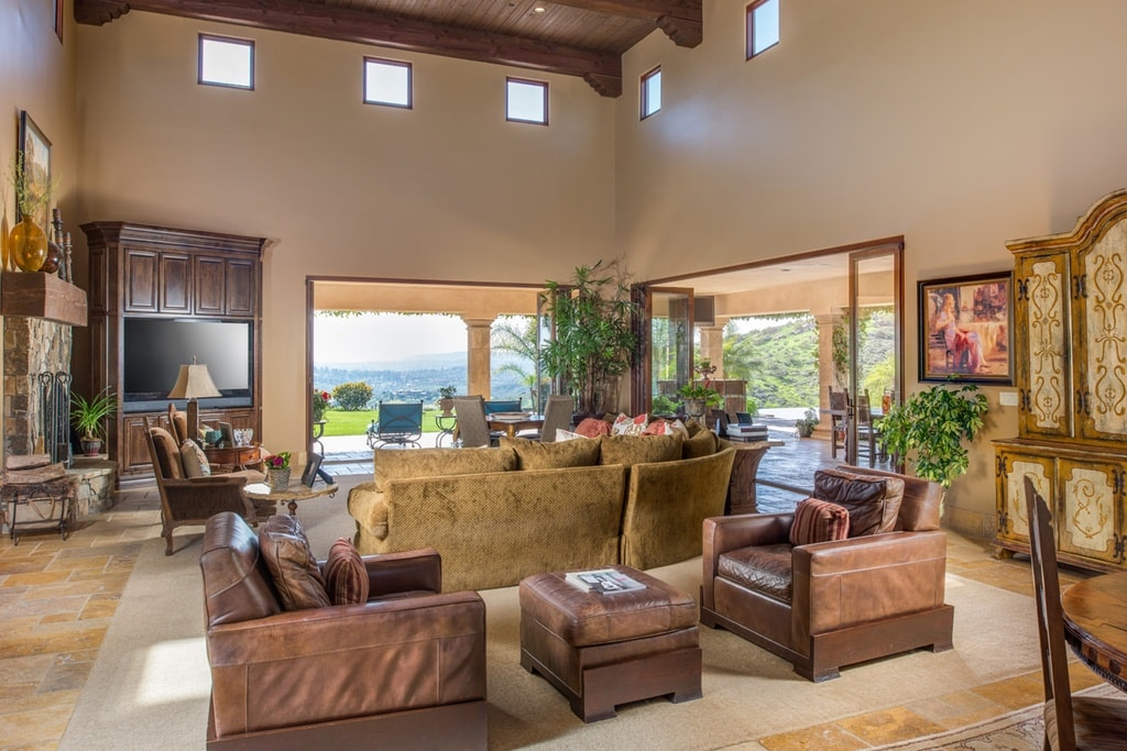 The spacious living room has various sofas and armchairs that go well with the tall beige walls. These are then topped with rows of small transom windows that brighten the wooden ceiling. Image courtesy of Toptenrealestatedeals.com.