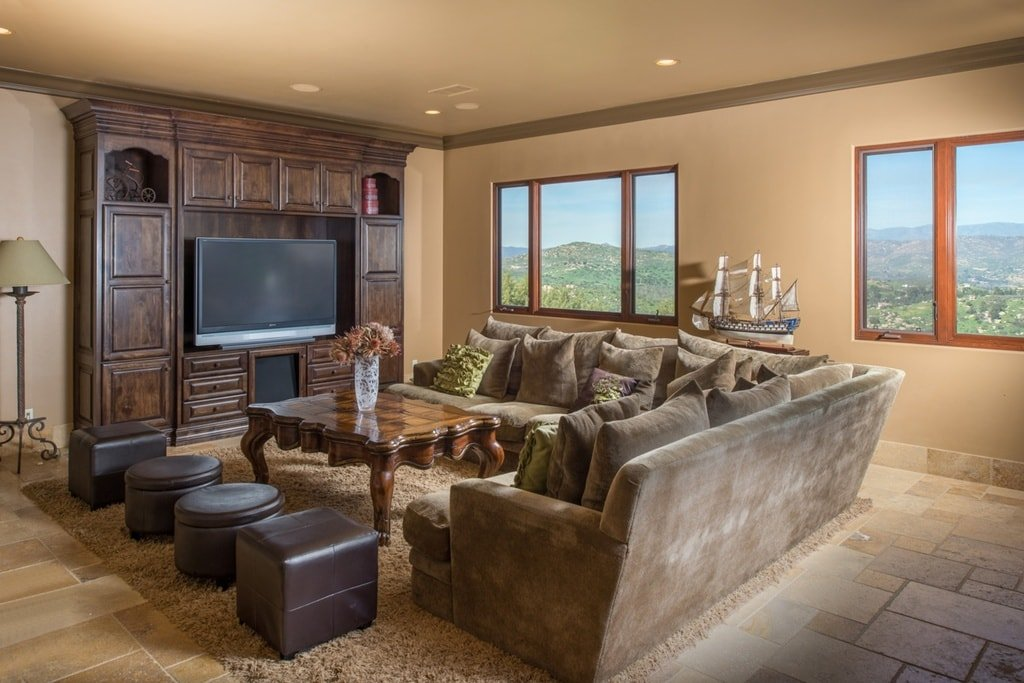 The media room has comfortable chocolate brown sofas paired with a wooden coffee table across from the dark wood structure that houses the TV. Image courtesy of Toptenrealestatedeals.com.