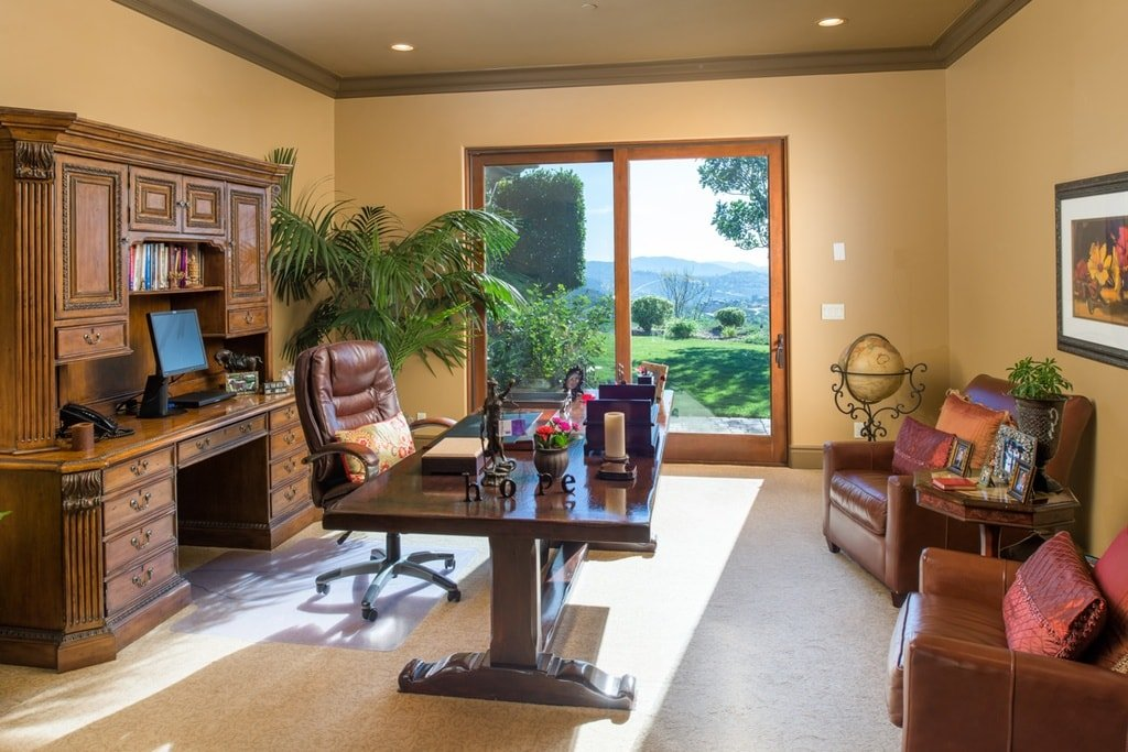 This is the home office that has a large wooden desk paired with a leather swivel chair adorned with a potted plant on the corner by the sliding glass doors. Image courtesy of Toptenrealestatedeals.com.
