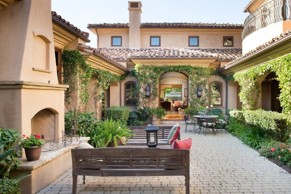 The patio courtyard at the side of the house has a park bench beside the outdoor fireplace. On the far side, you can see an outdoor dining area adorned with the surrounding green landscaping. Image courtesy of Toptenrealestatedeals.com.