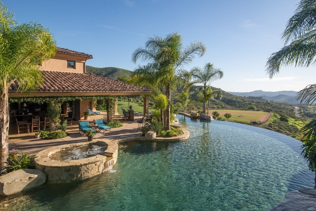 This is the large pool of the property with sweeping views of the surrounding landscape and adorned with tropical trees. Image courtesy of Toptenrealestatedeals.com.