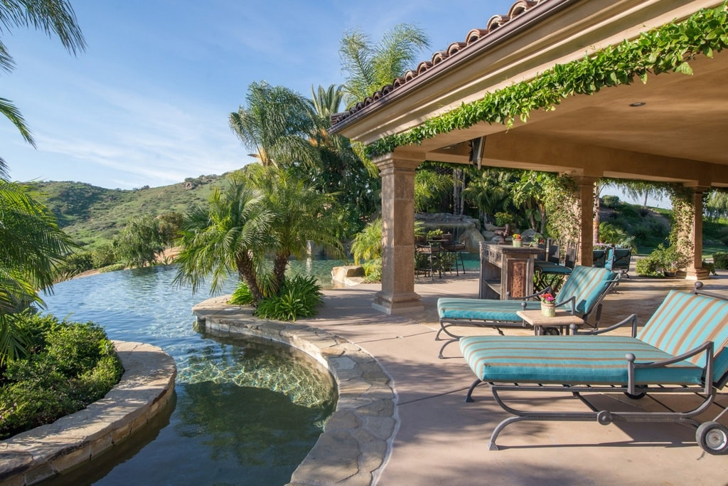 There is a couple of cushioned lawn chairs beside the pool to best enjoy the surrounding scenery and landscaping. Image courtesy of Toptenrealestatedeals.com.
