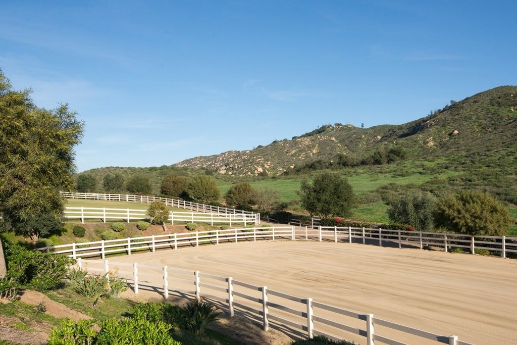This is the riding ring of the property surrounded by wooden fences to keep the horses from escaping. This is lined on the sides with trees and shrubs. Image courtesy of Toptenrealestatedeals.com.