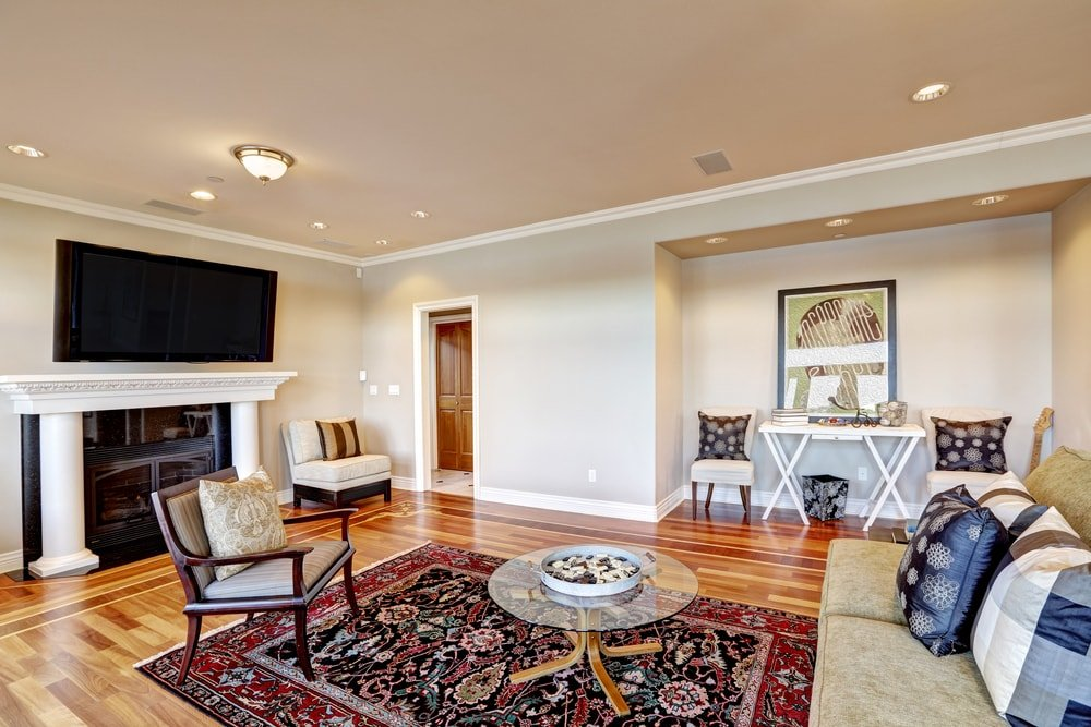 A family room with beige walls and ceiling to complement the hardwood flooring.