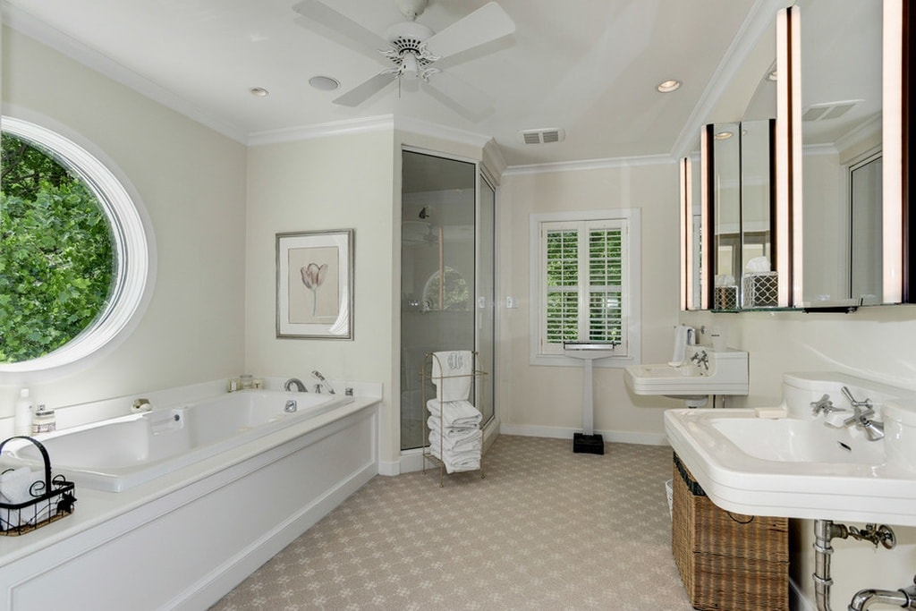 This is the primary bathroom with beige tiles on its floor to complement the white bathtub on one side and the white floating sinks on the other side. Image courtesy of Toptenrealestatedeals.com.
